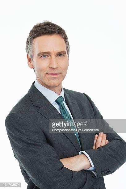 "portrait of mature businessman with arms folded - ""compassionate eye"" foto e immagini stock"