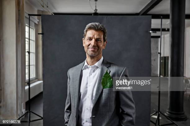 Portrait of mature businessman with leaf in pocket in front of black backdrop in loft