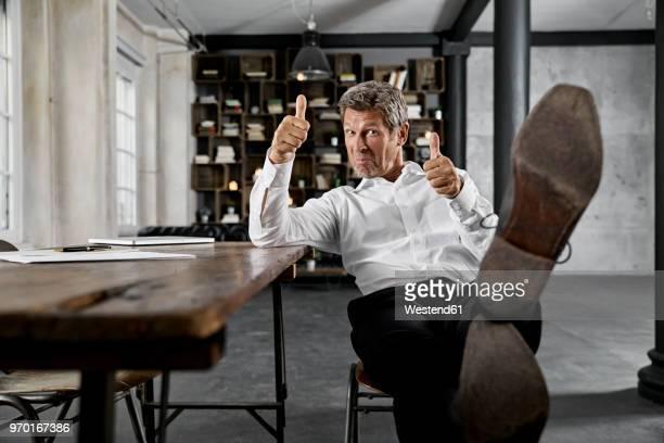 portrait of mature businessmanshowing thumbs up - esprimere a gesti foto e immagini stock