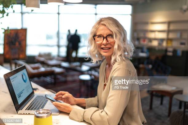 portrait of mature businesswoman analyzing investments on mobile phone and laptop at coworking - big data white stock pictures, royalty-free photos & images