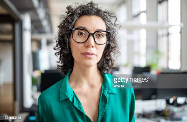 portrait of mature businesswoman in office - one mature woman only stock pictures, royalty-free photos & images
