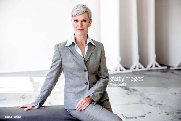 portrait of mature businesswoman  wearing grey pantsuit - pant suit stock pictures, royalty-free photos & images