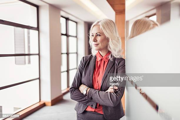 Portrait of mature businesswoman with arms folded at office doorway
