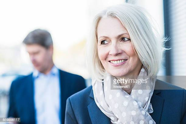 Portrait of mature businesswoman with man in background
