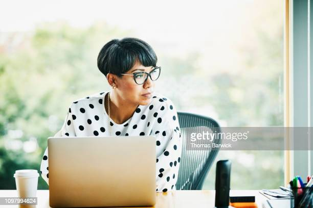 portrait of mature businesswoman working on laptop at workstation in office - contemplation office ストックフォトと画像