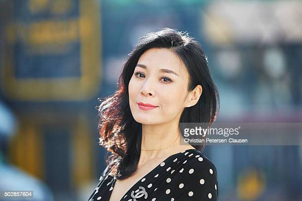 Portrait of mature Chinese businesswoman smiling outside