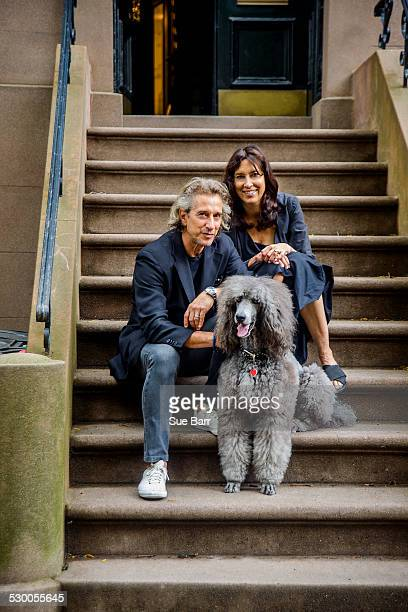 Portrait of mature couple and their poodle sitting on apartment stairway