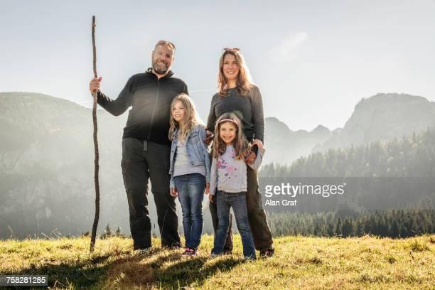 portrait of mature couple and two daughters in sunlit mountain landscape, bavaria, germany - familie mit zwei kindern stock-fotos und bilder