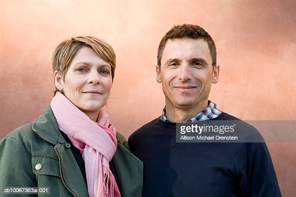 Portrait of mature couple in front of wall