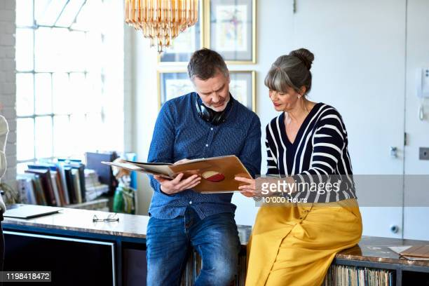 portrait of mature couple looking at vinyl record - couple relationship stock pictures, royalty-free photos & images