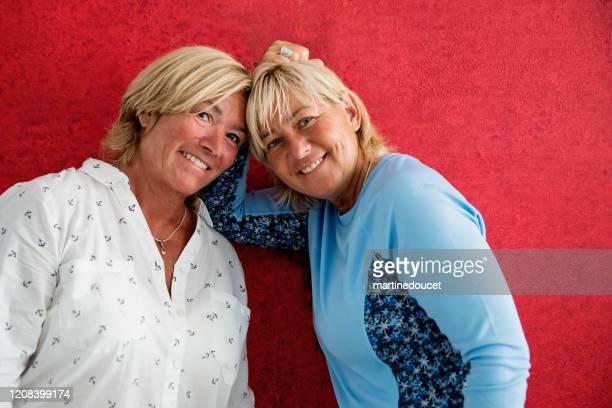 """retrato de parejas maduras de mujeres lgbtq posando en pared roja. - """"martine doucet"""" or martinedoucet fotografías e imágenes de stock"""