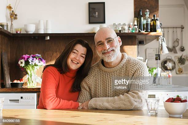 Portrait of mature couple sitting by table at home