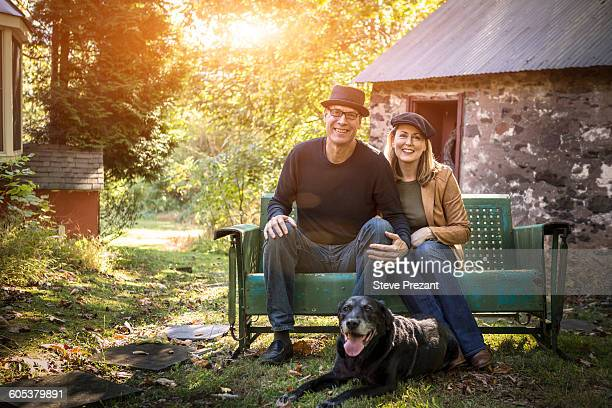 Portrait of mature couple with dog, sitting on bench, outdoors