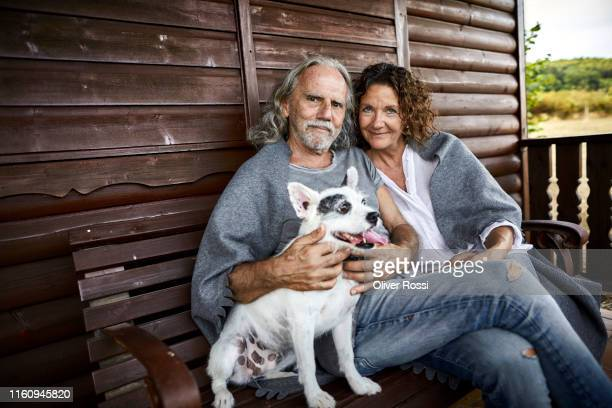 portrait of mature couple with dog sitting on porch of a log cabin - linda oliver fotografías e imágenes de stock