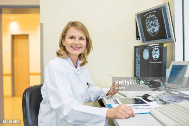 Portrait of mature doctor with CT scan reports