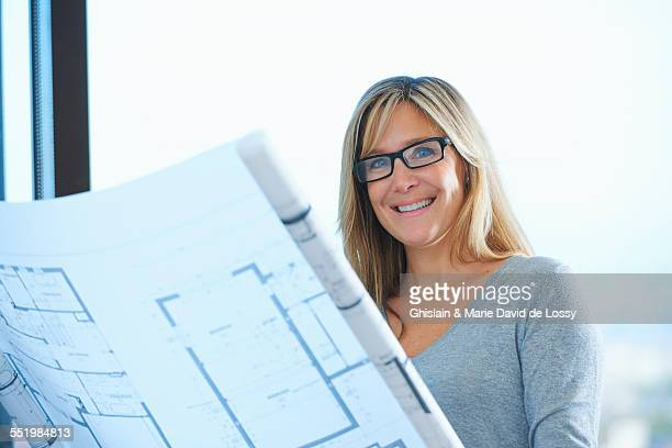 portrait of mature female architect with plans in office - real estate developer stock pictures, royalty-free photos & images
