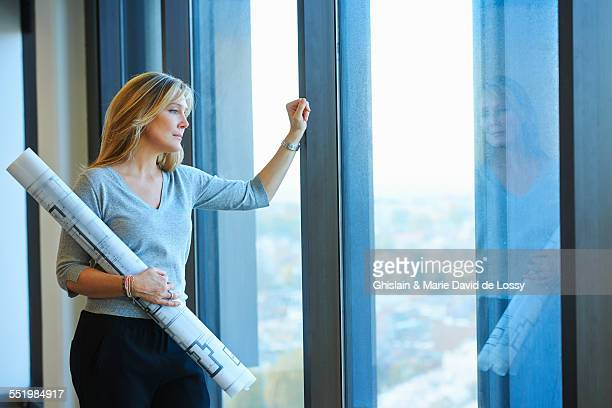Portrait of mature female architect with plans in skyscraper office, Brussels, Belgium