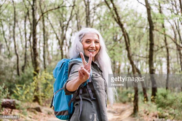 Portrait of mature female backpacker giving peace sign in forest, Scandicci, Tuscany, Italy