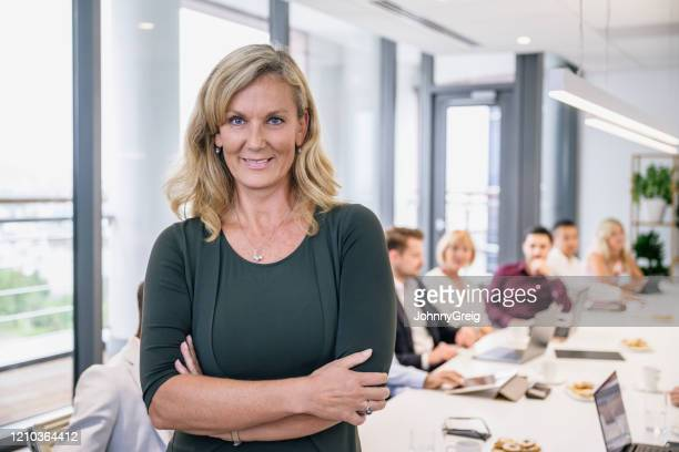 portrait of mature female ceo in corporate board room - mid adult men stock pictures, royalty-free photos & images