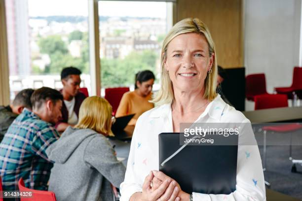 Portrait of mature female lecturer holding folder in classroom, smiling