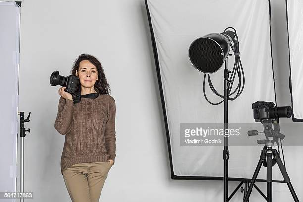 portrait of mature female photographer with camera in photo studio - photo shoot photos et images de collection