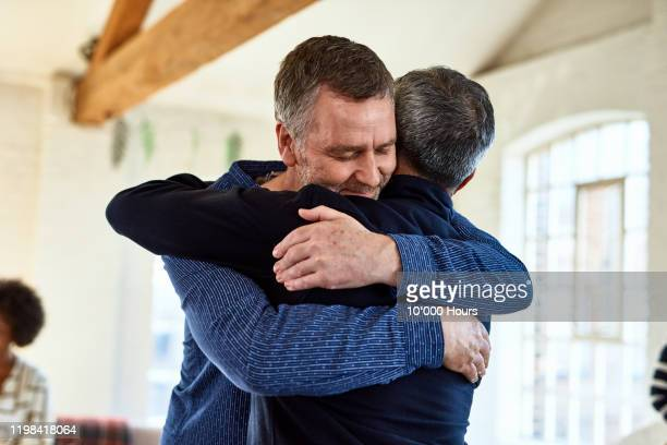 portrait of mature friends embracing with arms around each other - close to stock pictures, royalty-free photos & images