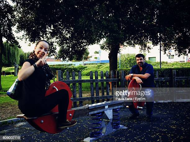 Portrait Of Mature Friends Sitting On Seesaw At Park