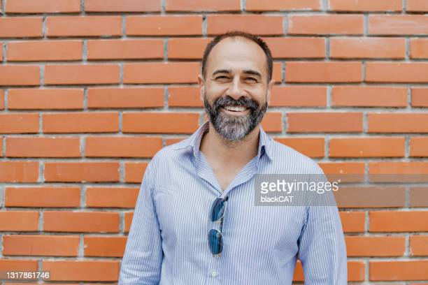 portrait of mature good looking man in front of the brick wall - one man only stock pictures, royalty-free photos & images
