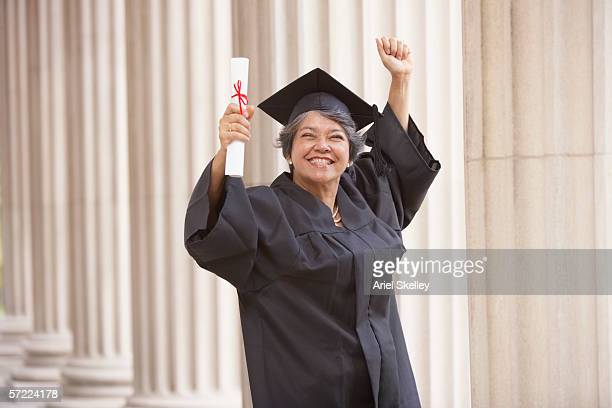 portrait of mature graduate in cap and gown - graduation gown stock pictures, royalty-free photos & images