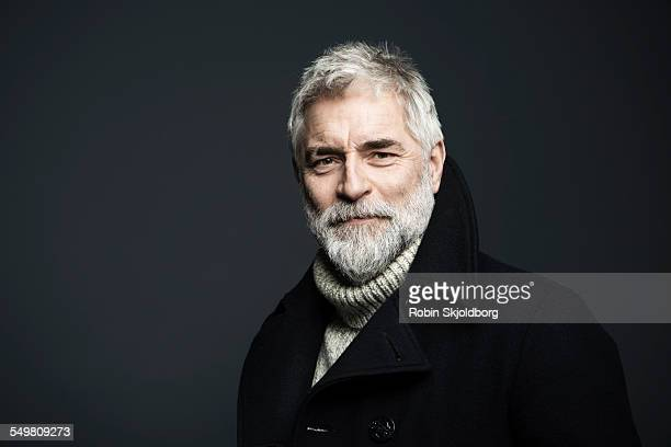 portrait of mature grey haired man in coat - handsome 50 year old men stock photos and pictures