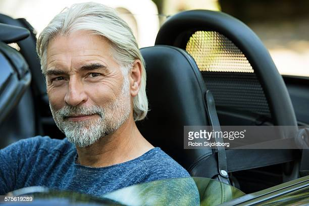 portrait of mature grey haired man in open car - handsome 50 year old men stock photos and pictures