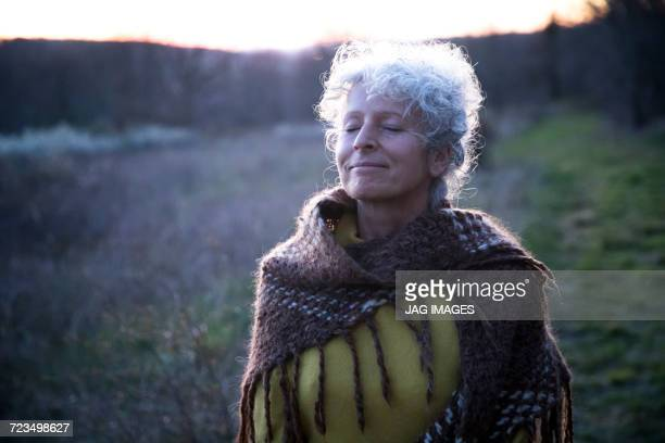 Portrait of mature grey haired woman with eyes closed in dusk landscape