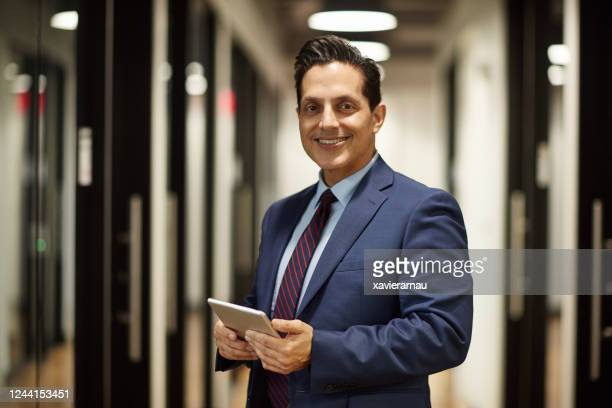 portrait of mature hispanic ceo using digital tablet - chief executive officer stock pictures, royalty-free photos & images