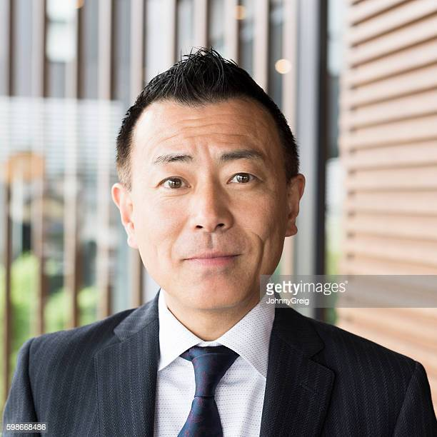 Portrait of mature Japanese businessman looking towards camera