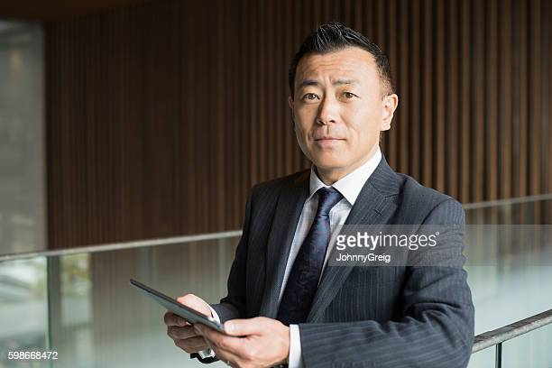 Portrait of mature Japanese businessman with tablet