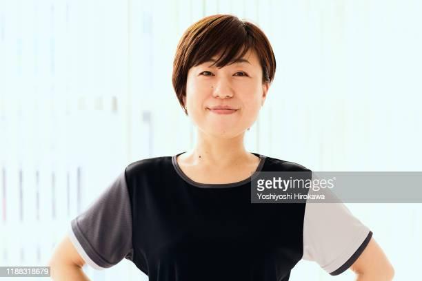portrait of mature japanese woman in fitness studio - スポーツ  ストックフォトと画像