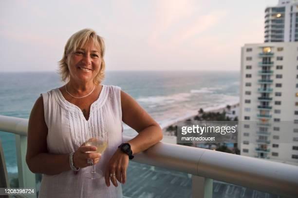 """portret van rijpe vrouw lgbtq op balkon bij schemering. - """"martine doucet"""" or martinedoucet stockfoto's en -beelden"""