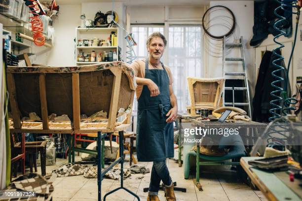 portrait of mature male craftsperson standing by incomplete sofa in upholstery workshop - emprendedor fotografías e imágenes de stock