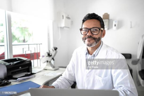 portrait of mature male doctor using laptop at hospital - eye doctor stock pictures, royalty-free photos & images
