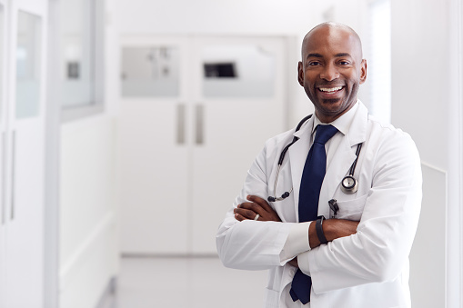 Portrait Of Mature Male Doctor Wearing White Coat Standing In Hospital Corridor 1203995945