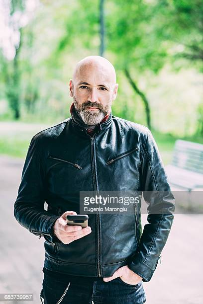 Portrait of mature male motorcyclist holding smartphone