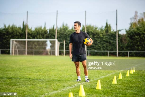 portrait d'un homme mature prêt à entraîner de jeunes footballeurs - stage sportif photos et images de collection