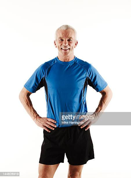 portrait of mature male runner smiling - running shorts stock pictures, royalty-free photos & images