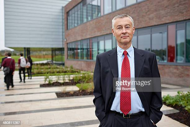 portrait of mature male teacher outside school - school principal stock pictures, royalty-free photos & images