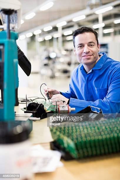 Portrait of mature male technician working on circuit board at desk in industry