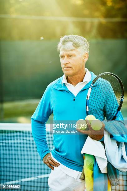 Portrait of mature male tennis player after early morning workout