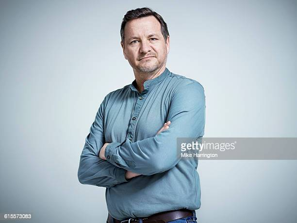 portrait of mature male with arms crossed - arme verschränkt stock-fotos und bilder