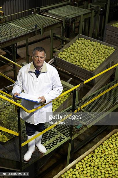 Portrait of mature male workers inside apple processing factory