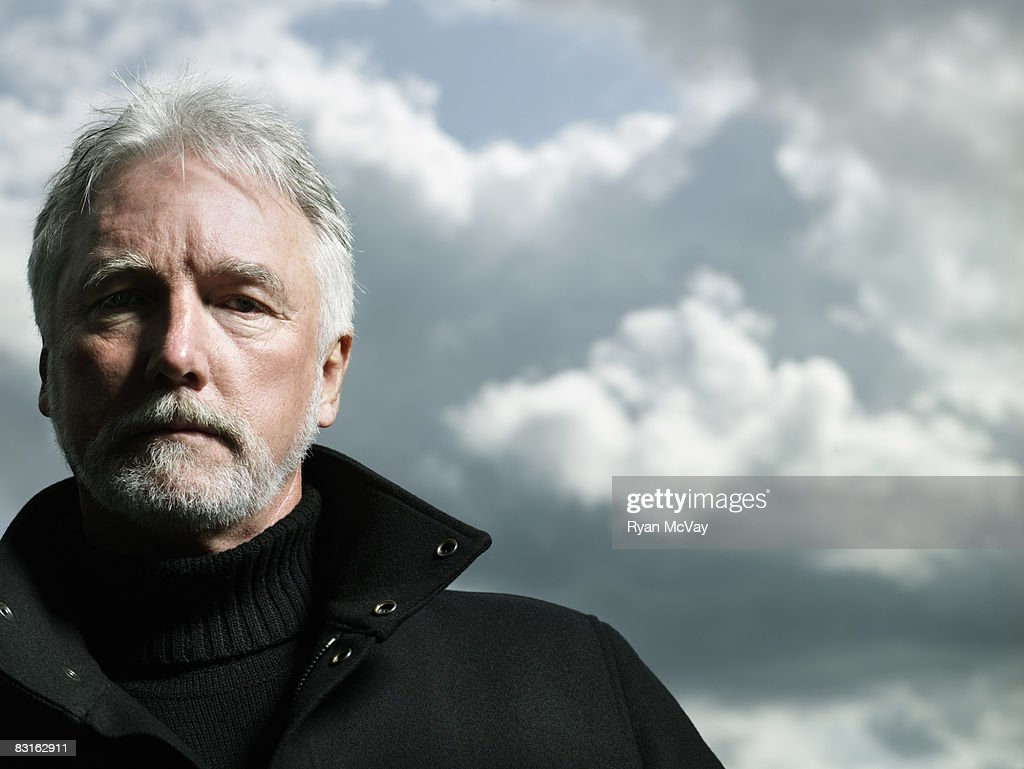 Portrait of mature man against stormy sky. : Stock Photo
