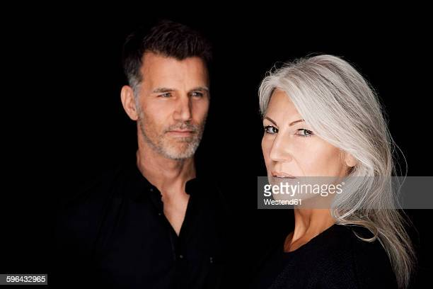 Portrait of mature man and mature woman wearing black clothes in front of black background